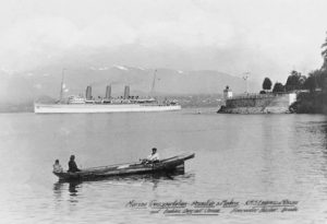 Empress of Russia sails from Vancouver, passing a native canoe